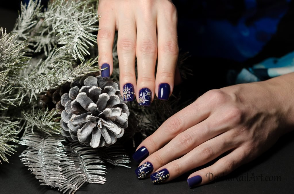 Christmas diamond snowflake nail design in the blue color