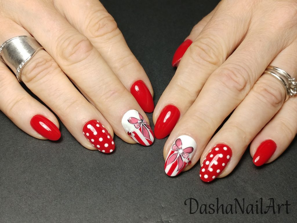 Cute classic red nails with hand drawn ribbons, dots and shiny diamonds