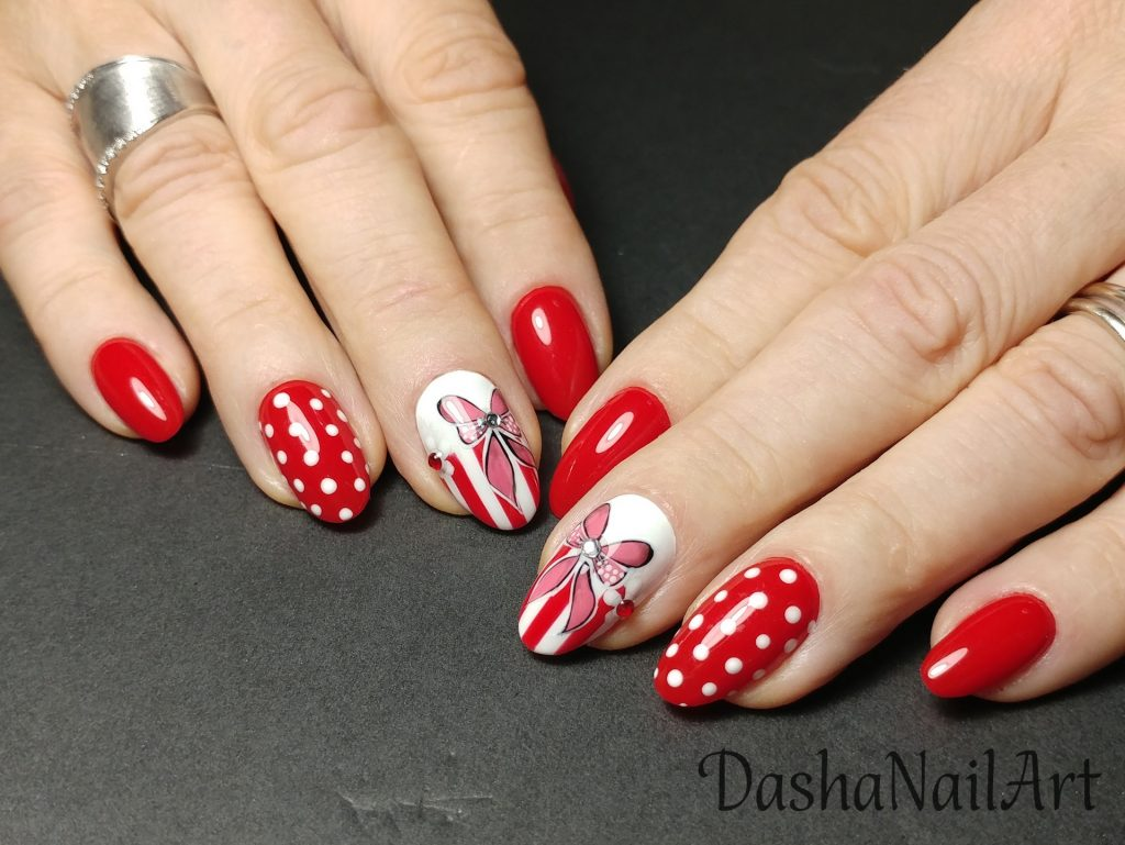 Perfect red nails with hand drawn bows and white dots