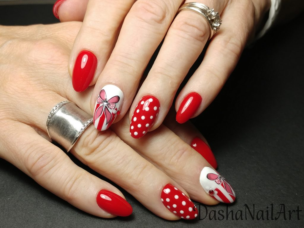 Elegant red nails with hand drawn bows and white dots