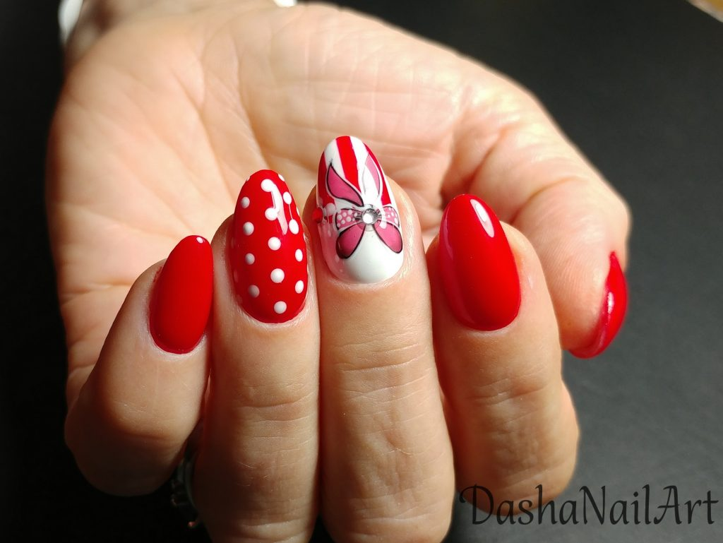 Royal red nails with hand drawn bows and white dots
