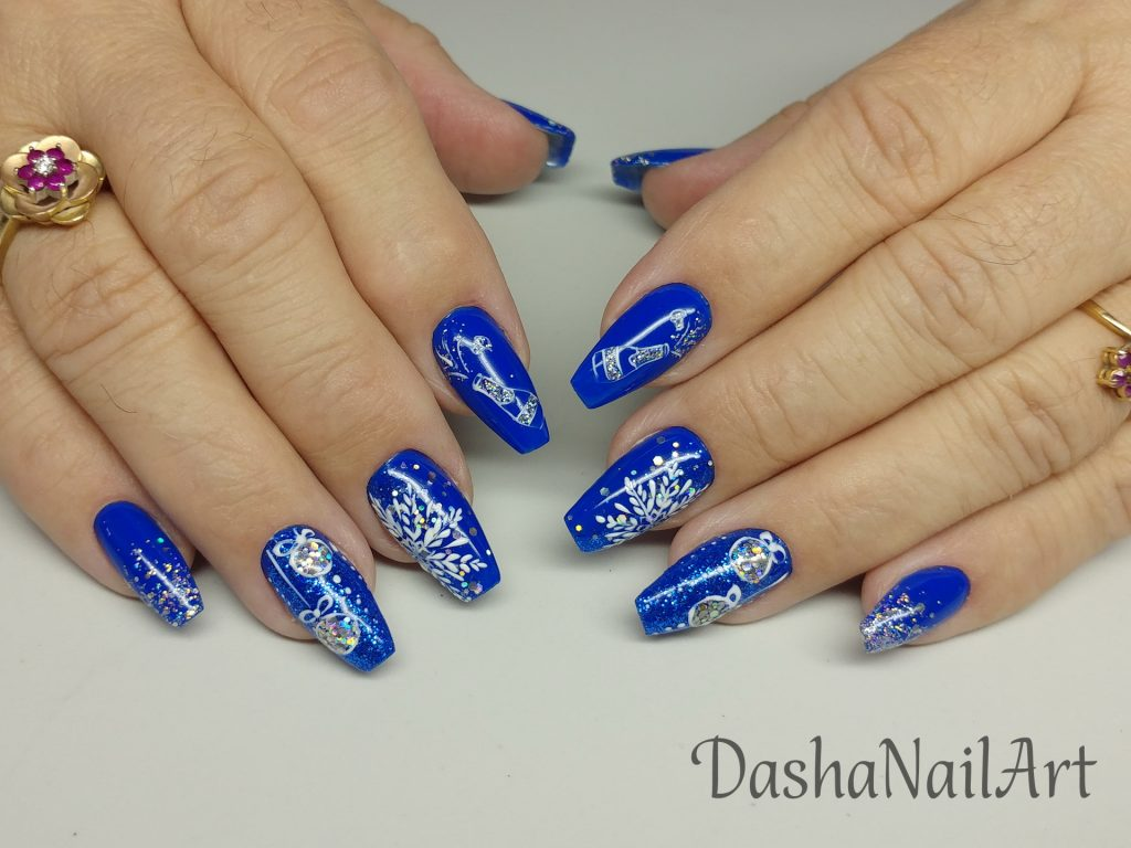 New Year blue nails with glitters, tree decoration, snowflakes and champagne