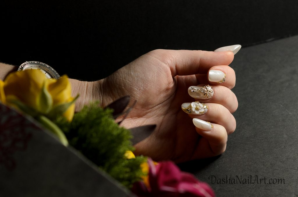 Short modern almond nails with chrome stamping and 3D flowers, jewellery and diamonds